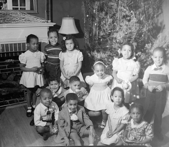 Group portrait: Young boys and girls posing infront of fireplace and Christmas tree, December 1949, Paul Henderson, MdHS, HEN.02.03-034.