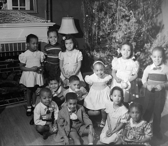Group portrait: Young boys and girls posing in front of fireplace and Christmas tree, December 1949, Paul Henderson, MdHS, HEN.02.03-034.